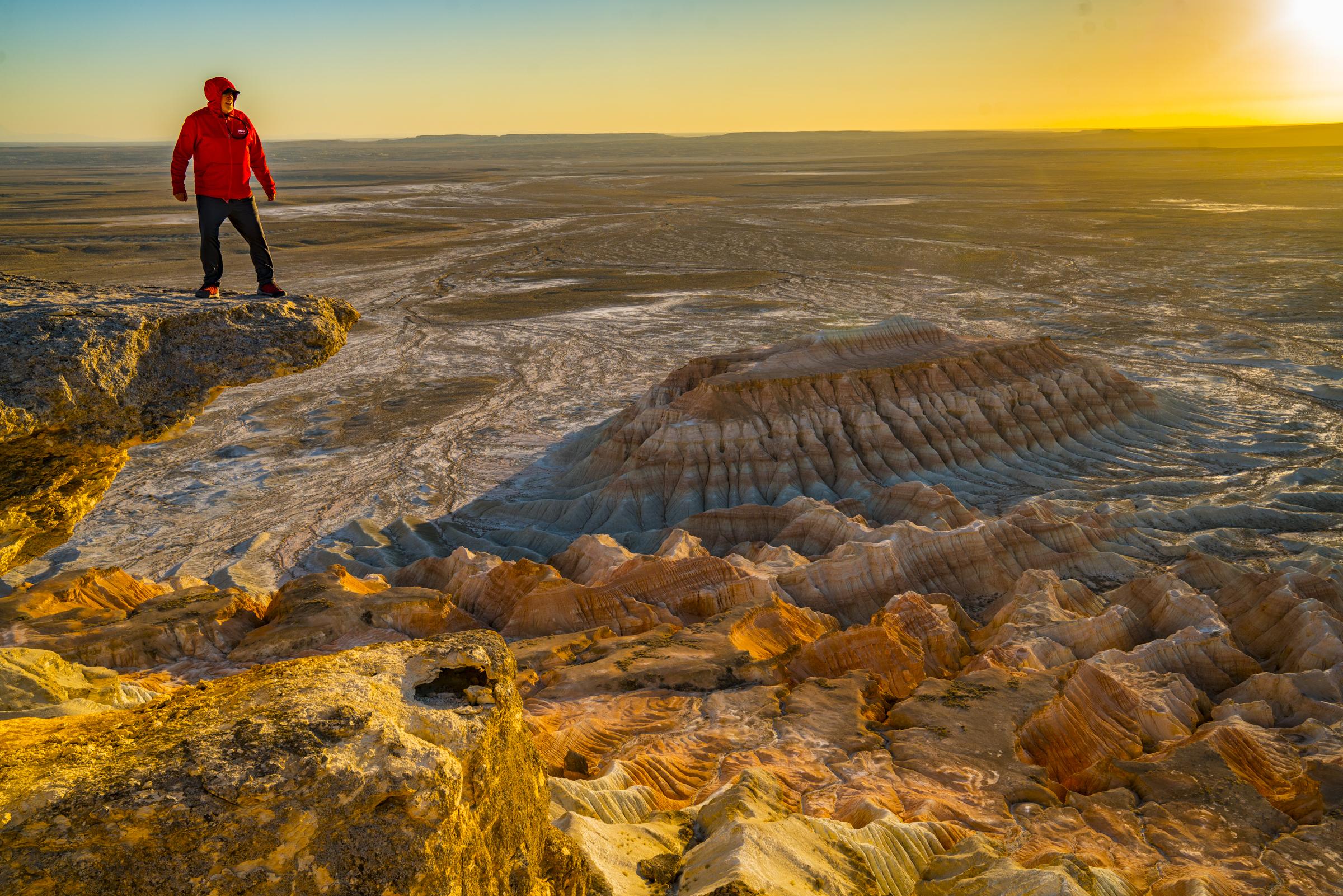 Hiker on precipce above Yangikala Canyon, Turkmenistan photographed by Tom Till